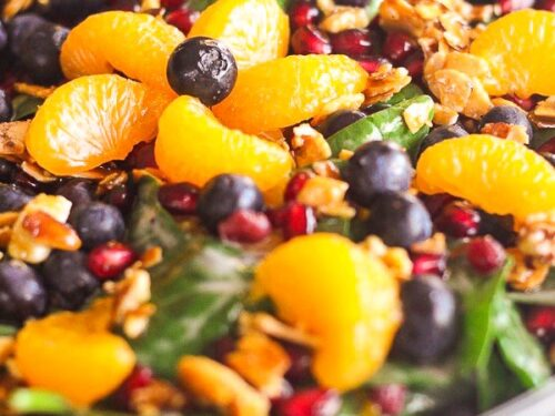 Mandarin Spinach Salad with Candied Pecans, blueberries, and pomegranite seeds in a big glass bowl.