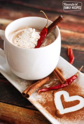 Mayan Hot Chocolate topped with whipped cream and cinnamon sticks in a white mug.