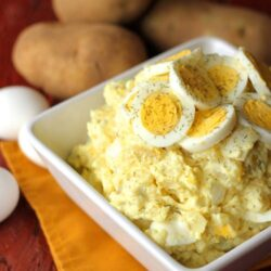 potato salad with egg slices on top in a white bowl and potatoes in background