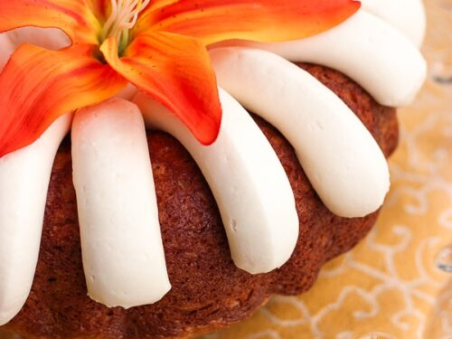 Nothing Bundt Cake's Carrot Cake topped with an orange flower on a glass tray.