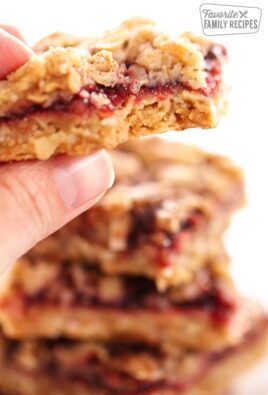 Close up of a hand holding an Oatmeal Raspberry Crumb Bar