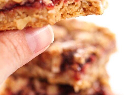 Close up of a hand holding an Oatmeal Raspberry Crumb Bar