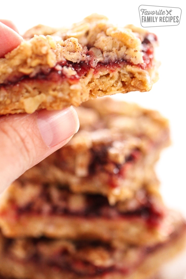Close up of a hand holding a Raspberry Oatmeal Bar with a bite taken out of it
