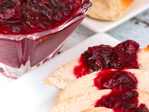 Orange Cranberry Sauce over slices of turkey with rolls in the background.