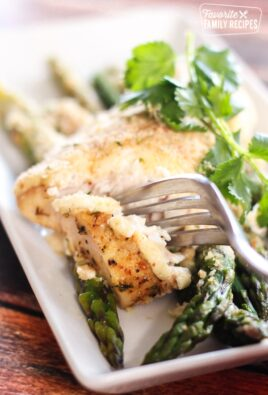 parmesan herb baked mahi mahi on a white plate with asparagus and garnish