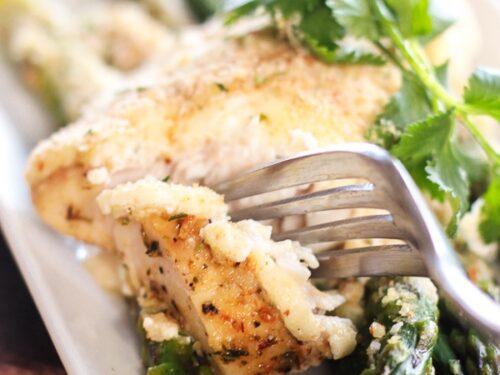 parmesan herb baked mahi mahi on a white plate with asparagus and garnish