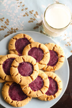 8 Peanut Butter and Jelly Cookies on a blue plate with a glass of milk on the side.