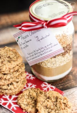 A plate of cookies with a jar of Pecan Chewies Mix in a mason jar on the side