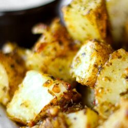 Close up of Pesto Potatoes with a side of ranch in the background.