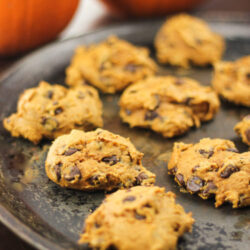 Plate of pumpkin chocolate chip drop cookies with two pumpkins behind