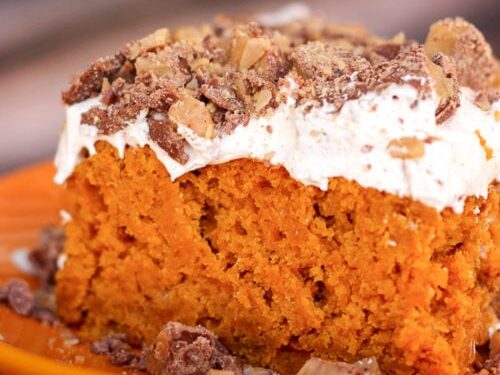 pumpkin poke cake on an orange plate with crumbles on the side