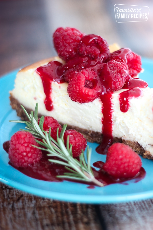 Cheesecake slice with Raspberry Sauce and raspberries drizzled over on a blue plate.