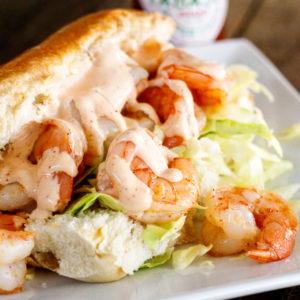 Shrimp po boy sandwich with creamy cajun sauce on a hoagie bun with shredded cabbage