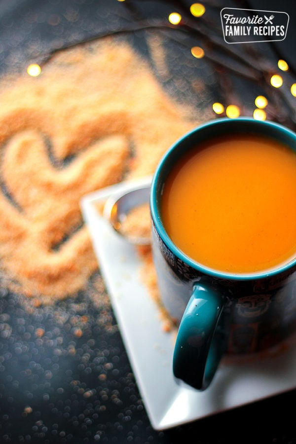 A cup of hot Wassail in a blue mug with Wassil mix on the counter next to it.
