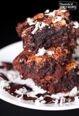 3 almond joy brownies stacked on top of each other covered in chocolate sauce and coconut flakes on a plate.