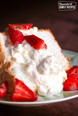 Slice of angel food cake covered in pineapple whip and slices of strawberries on a plate.