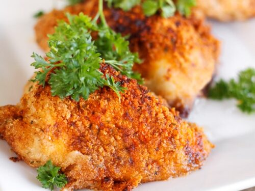 3 pieces of Paprika & Parmesan Chicken topped with a garnish on a white plate
