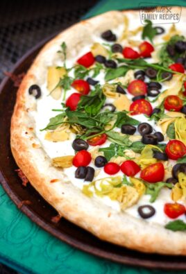 Antipasto Pizza on a metal circular tray.