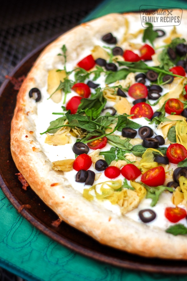 Antipasto Pizza on a metal circular tray.