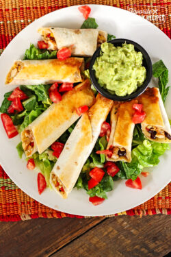 6 Baked Chicken Firecrackers on a plate with lettuce and tomatoes and a small black bowl of guacamole.
