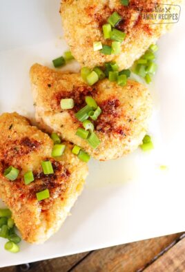 3 pieces of baked garlic chicken topped with green onions on a white plate.