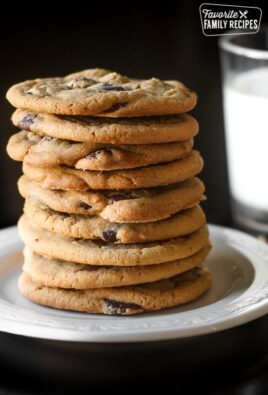 Bakery Chocolate Chip Cookies Stacked on a white Plate with a glass of milk in the background