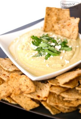 Basil Parmesan Hummus in a white Bowl with Crackers
