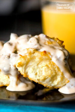 2 Biscuits covered Sausage Gravy on a plate with a glass of orange juice in the background.