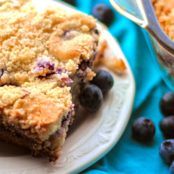 A piece of blueberry cream cheese coffee cake on a white serving plate with fresh blueberries