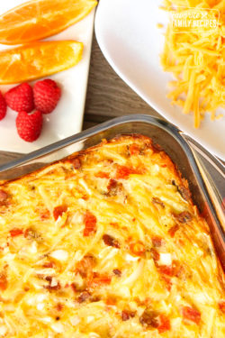 hash brown breakfast casserole in a pan with fruit and cheese on the side.