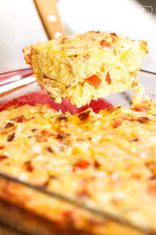 slice of hash brown break fast casserole being lifted out of a pan with a spatula.