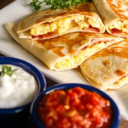 Breakfast Quesadillas on a white plate with a side of salsa and sour cream.