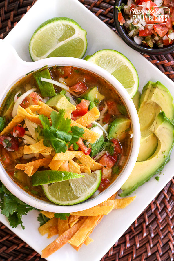 Above view of Cafe Rio Tortilla Soup Recipe in a white bowl with tortilla chips and limes