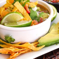 Cafe Rio Soup in a bowl with tortilla strips and limes