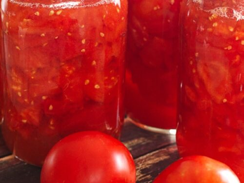 3 mason jars of Canned Diced Tomatoes with 2 fresh tomatoes on the side