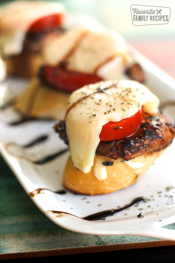Caprese Chicken Sliders on a Sourdough Baguette on a white tray.