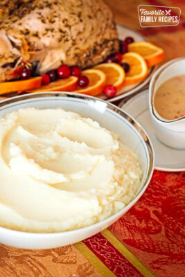 Cauliflower mashed potatoes in a white serving bowl with gravy and turkey in the background