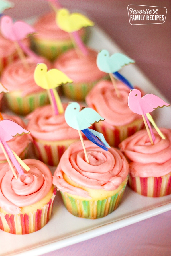 Cherry Limeade Cupcakes with paper bird toppers on a white tray.