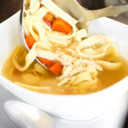 A square white bowl filled with homemade chicken noodle soup