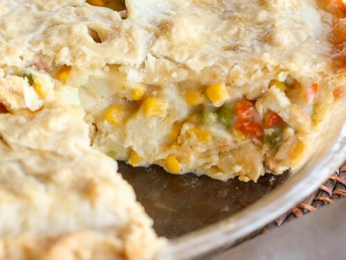 A chicken pot pie with vegetables in a pie plate with a slice cut out