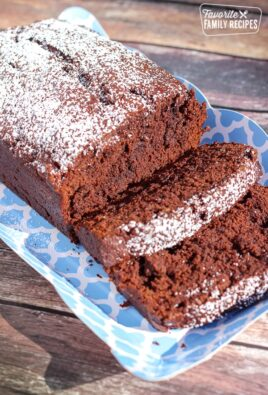 Sliced Chocolate Banana Bread sprinkled in powdered sugar on a blue tray.