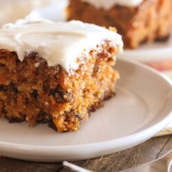 A slice of classic carrot cake on a white plate with another piece in the background.