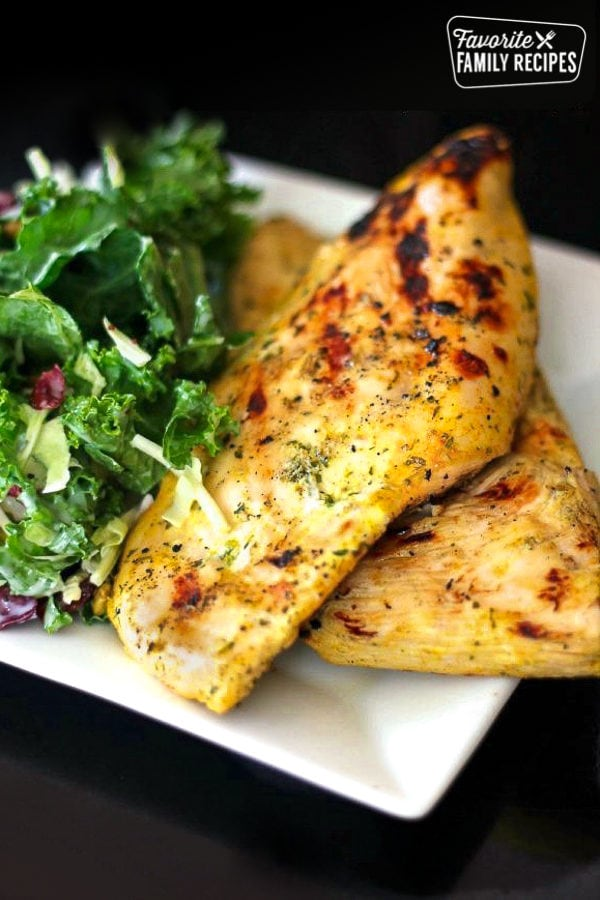 Two pieces of Coconut Curry Grilled Chicken with a salad on the side.