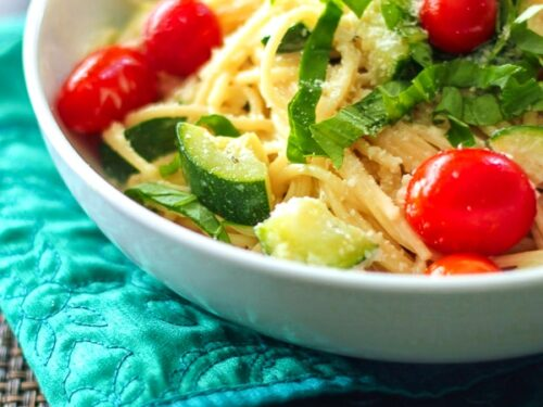 Creamy Basil Noodles topped with vegetables in a white bowl.