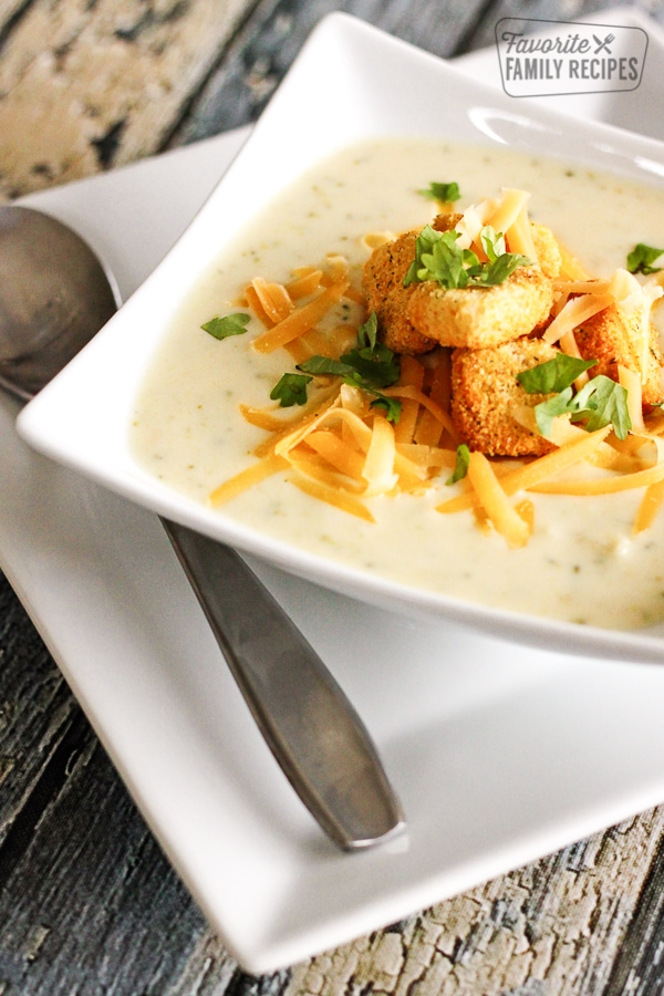 Creamy Broccoli Cauliflower Soup topped with cheese and croutons in a white bowl.