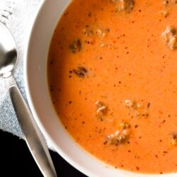 Creamy Tomato Basil Soup with Sausage in a white bowl with a spoon on the side.