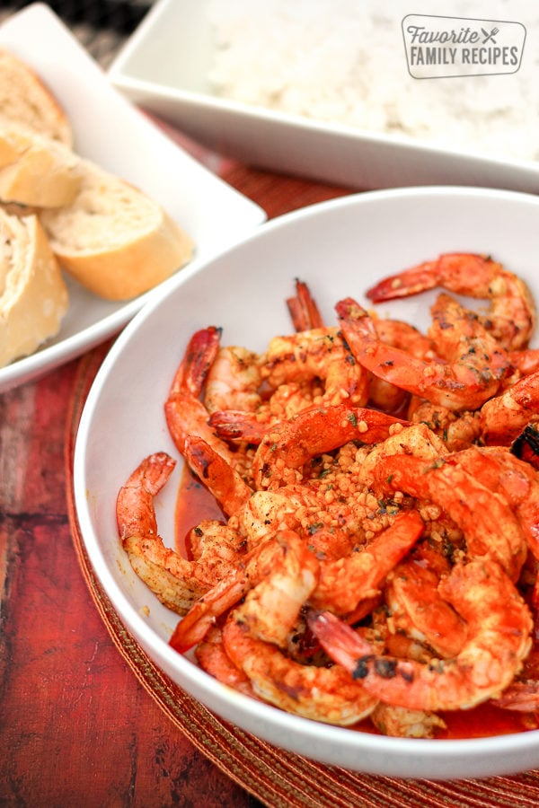 Creole Butter Shrimp in a white bowl with bread on the side.