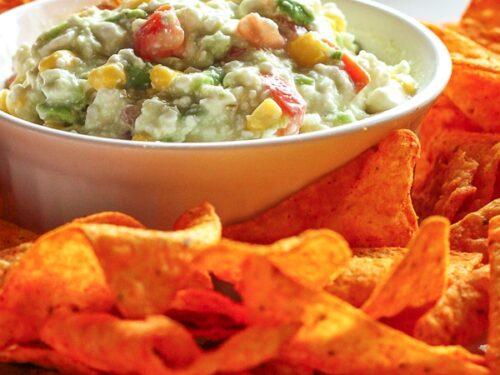 Dorito Dip in a white bowl surrounded by Nacho Cheese Doritos