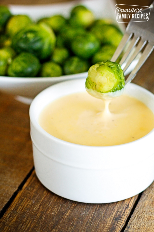 Brussel Sprout being dipped into Cheese Sauce