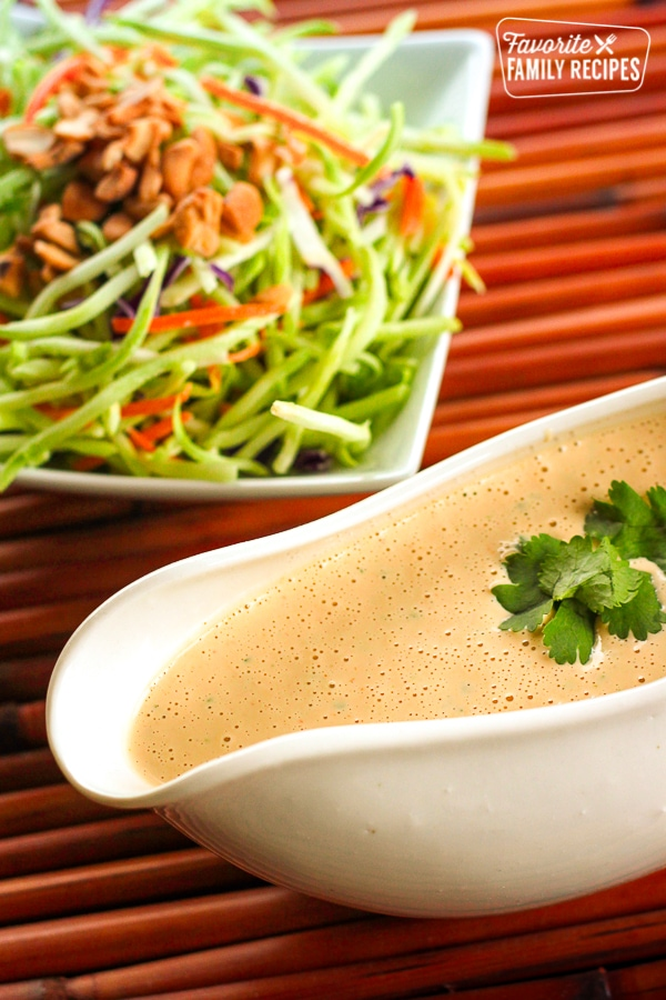 Easy Creamy Thai Peanut Dressing in a gravy boat with a salad in the background.